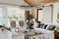 a farmhouse living room with much natural wood, a crystal chandelier, cozy and simple furniture and a barn door