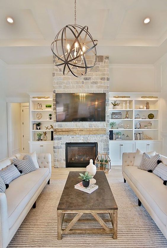 a lovely modern farmhouse living room with a brick clad fireplace, elegant sofas, a rustic coffee table and a sphere pendant lamp