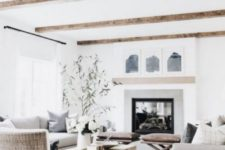 a modern farmhouse living room with wooden beams on the ceiling, neutral furniture, a wooden living edge table, a modern fireplace