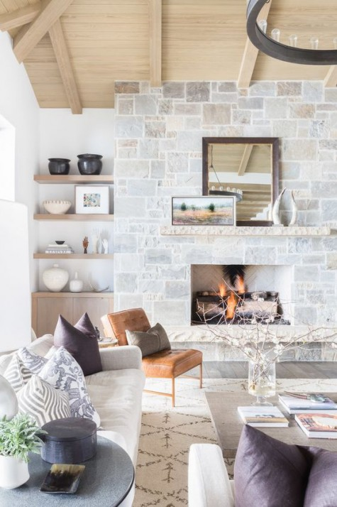 a modern farmhouse living space with a stone clad fireplace, a leather chair, built in shelves, a white sofa