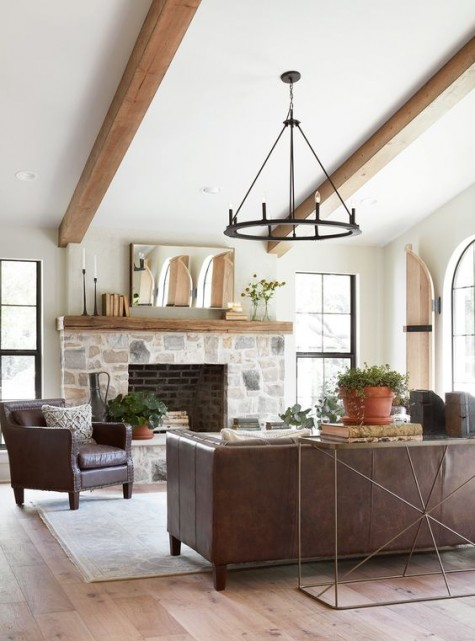 a modern laconic farmhouse living room with a stone fireplace, leather furniture, a vintage chandelier and potted greenery