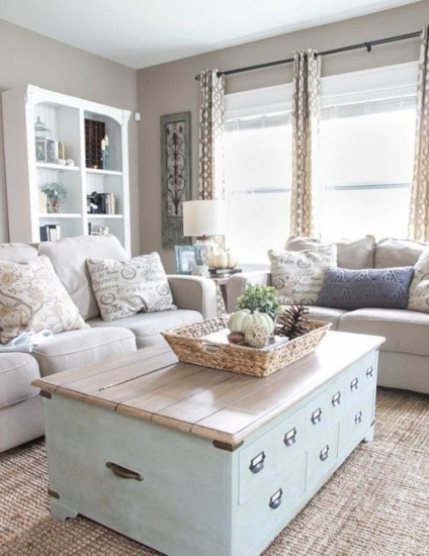 a neutral and pastel farmhouse living room with an aqua chest table, neutral sofas, a large storage unit and printed curtains