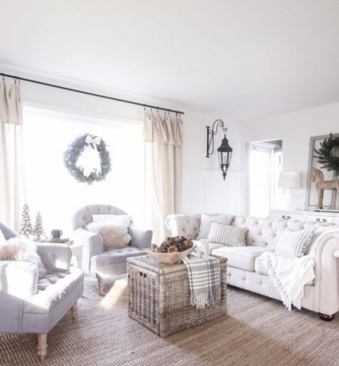 a neutral and pastel farmhouse space with blue chairs, a white sofa, a basket box as a coffee table and a jute rug