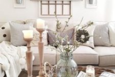 a neutral farmhouse living room with neutral upholstery and pillows, much wood in decor, a basket and metal planters