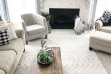 a neutral living room with comfy furniture, a wooden coffee table, a fireplace with a wooden mantel and some arrangements
