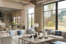 a rustic farmhouse living room with much light-colored wood,cremay furniture, a branch chandelier and printed pillows