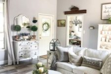 a small farmhouse living room done in neutrals, with much texture, a vintage chandelier, potted greenery and vintage decor