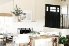 a small white farmhouse living room with white furniture, wooden tables and chairs, baskets for storage and a brick fireplace