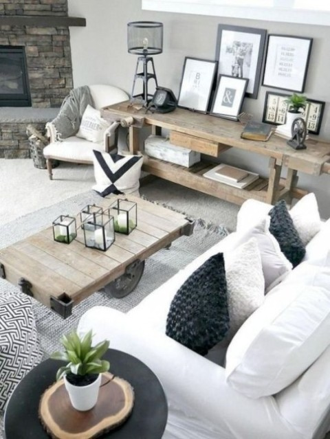 a stylish farmhouse living space with rough wooden tables, white upholstery, some prints and a faux stone clad fireplace