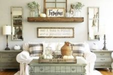 a vintage farmhouse living room with a green vintage chest as a coffee table, a white sofa with checked pillows, a wooden shelf and mirror window decor