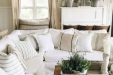 a vintage farmhouse living room with upholstered neutral furniture, neutral curtains, vintage decor and potted greenery