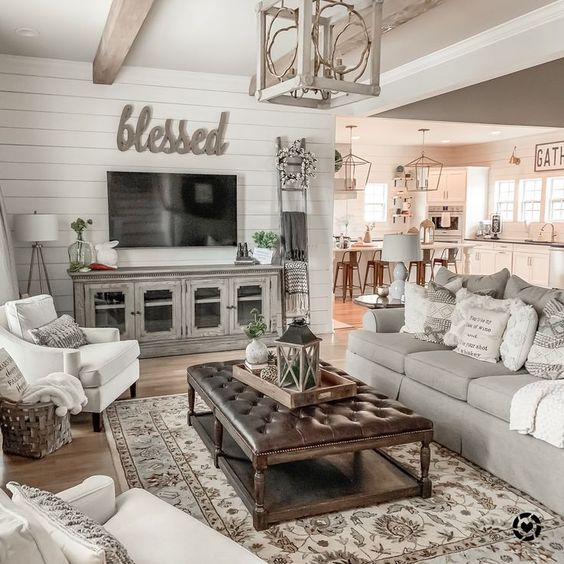 a vintage farmhouse living space with grey furniture, a stained ottoman with a leather top, a pendant lamp and printed pillows