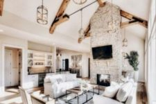 a welcoming farmhouse living room with a brick clad fireplace, white sofas and chairs, a rug and glass cylinder pendant lamps