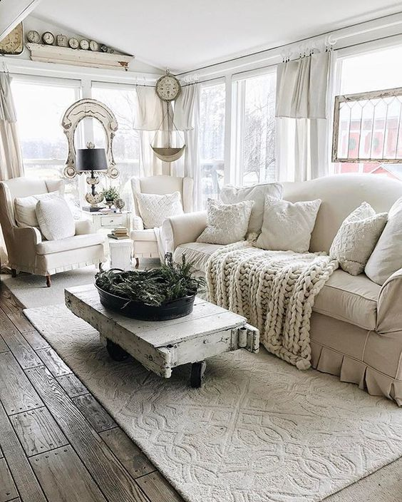 a white farmhouse living room with a shabby chic coffee table, shabby details and neutral textiles