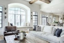 an airy farmhouse living room with a white sofa, a brown chair, a vintage whitewashed wooden coffee table and wooden beams