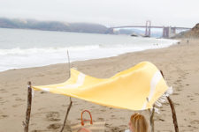 DIY boho beach tent of sticks and a shower curtain