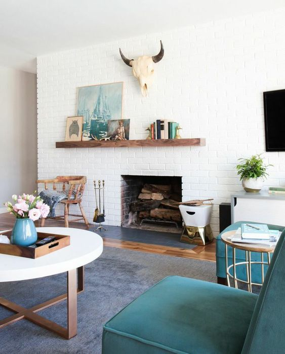 a modern farmhouse living room with white brick walls and touches of turquoise and teal