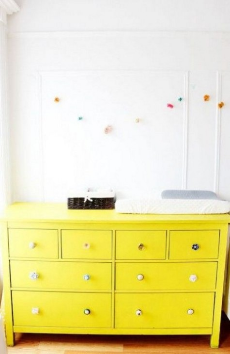 an IKEA Hemnes hack in bold yellow with different knobs will make a colorful statement in the nursery