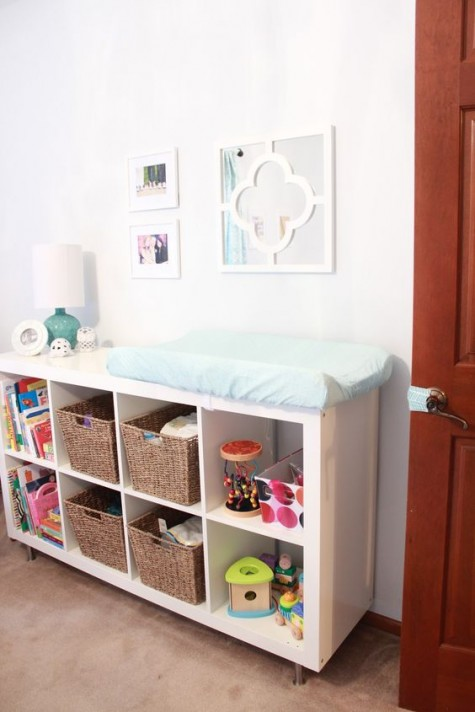 an IKEA Expedit wall unit with open storage spaces and baskets as a changing table