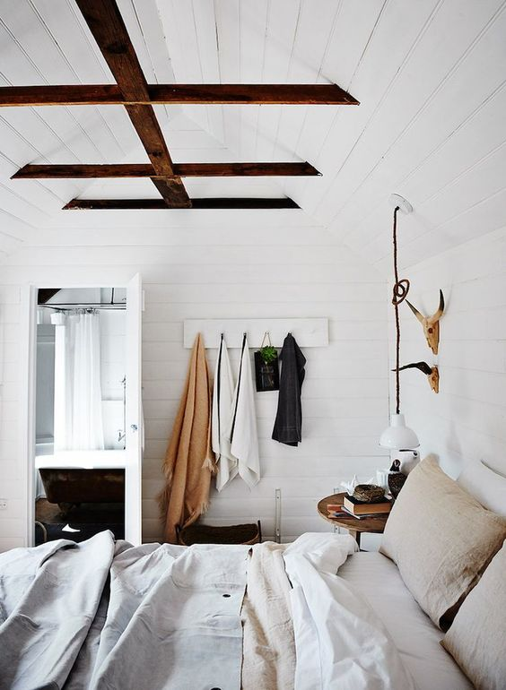 white wooden plank walls contrast dark wooden beams creatign a welcoming farmhouse bedroom