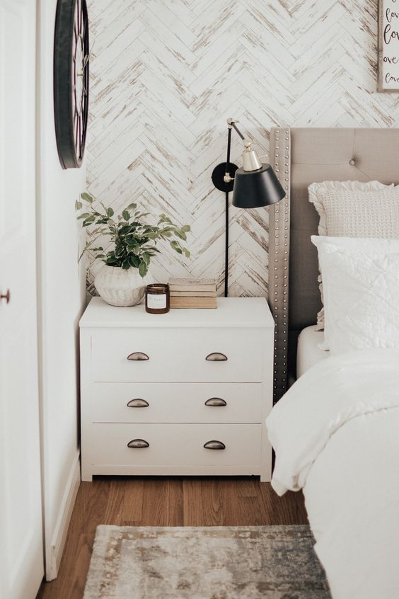 a bedroom with wooden walls clad in a herrignbone pattern and whitewashed for a nonchalant and chic look