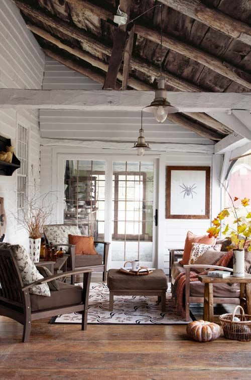 a cozy rustic living room done with white wooden walls and a dark wooden ceiling with beams