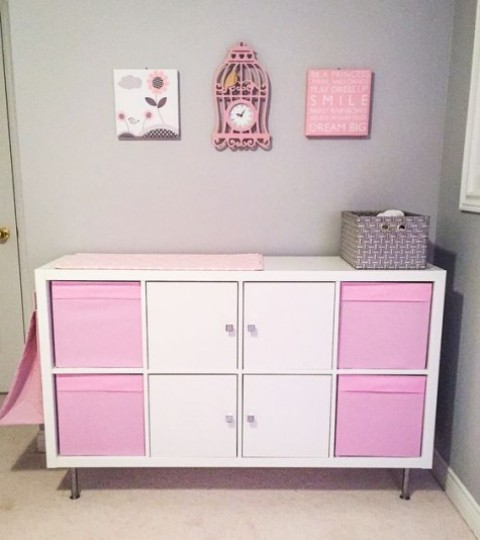 an IKEA Kallax shelf turned into a pink girlish changing table with storage compartments and boxes