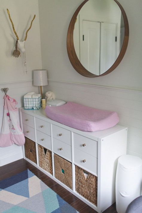 an IKEA Kallax shelf with drawers and woven baskets for a stylish changing table with a rustic touch