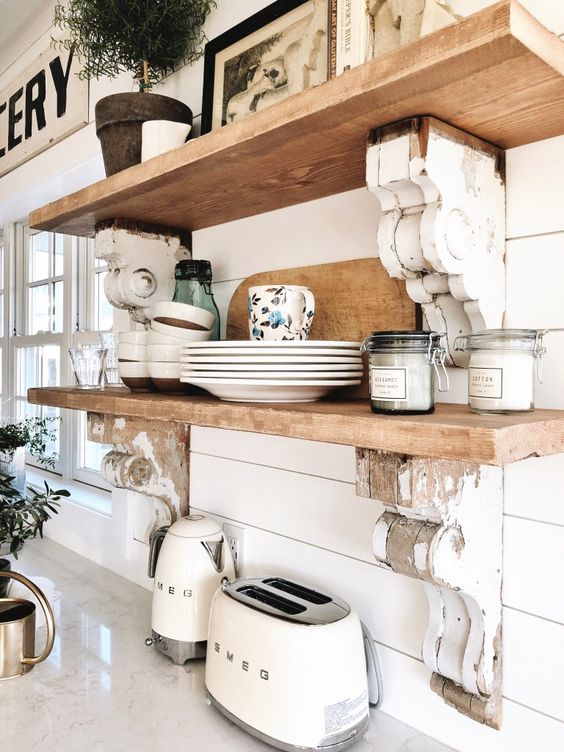white shiplap walls and naturally stained wooden shelves make up a chic and cool farmhouse kitchen
