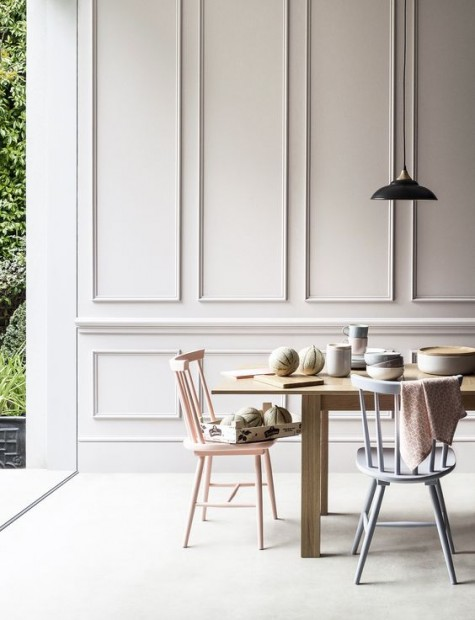 a contemporary dining space with white molded walls for a refined touch and simple furniture