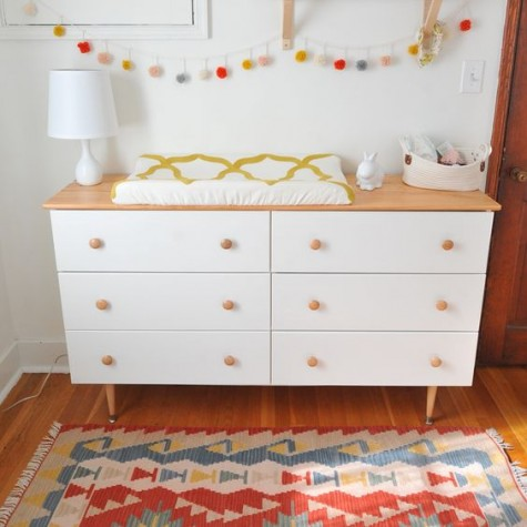 an IKEA Tarva dresser with a light-colored wooden top and matching pulls and legs used as a changing table