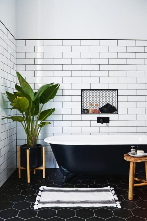 long white subway tiles with black grout and black hexagon ones on the floor with white grout