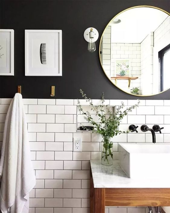 popular subway tiles are paired with a black wall and highlighted with black grout for a cool look