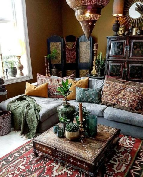 a Moroccan boho liivng room with a sectional sofa, printed pillows and rugs, a large Moroccan lantern, a wooden screen and a carved table