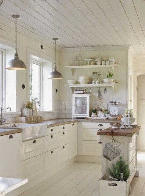 a beautiful white farmhouse kitchen with butcherblok countertops, pendant lamps and a white subway tile backsplash