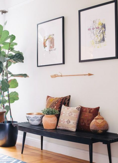 a black bench, printed folksy pillows, potted plants, and a mini gallery wall compose a quirky and chic space