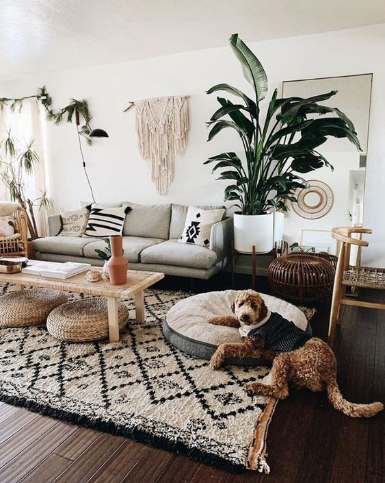 a bohi chic living room with a printed rug and pillows, a macrame hanging, potted plants and jute ottomans