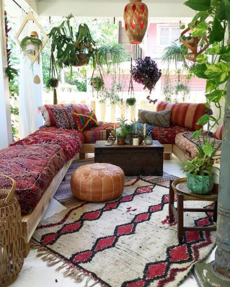 a boho Moroccan porch with a U shaped bench with boho upholstery, a bright rug, a leather ottoman and lots of potted plants