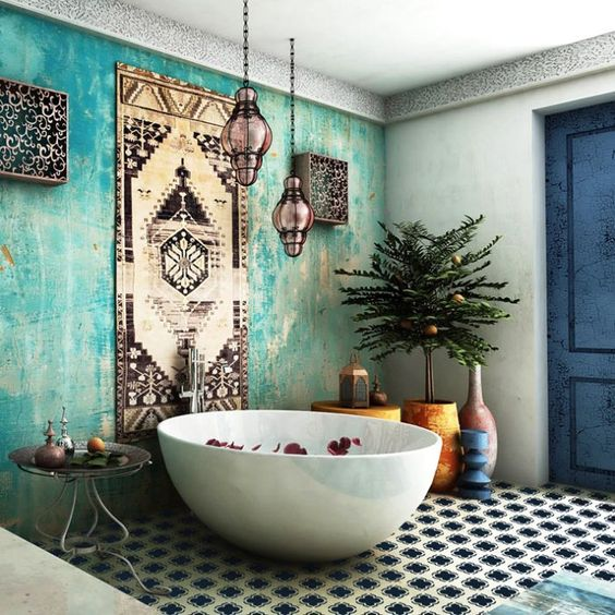 a boho bathroom with a Moroccan feel - an aqua plaster wall, a rug as an artwork and gorgeous Moroccan lanterns hanging