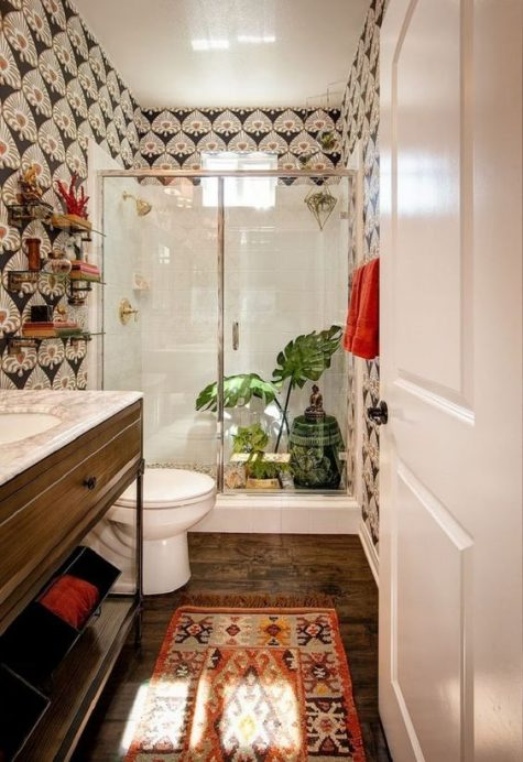 a boho bathroom with a boho rug, printed wallpaper on the walls, greenery and a porcelain side table