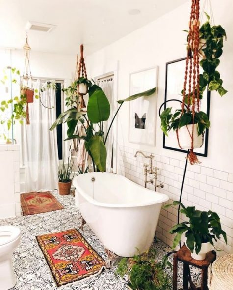 a boho bathroom with lots of potted greenery hanging nd standing, boho rugs and a mosaic tile floor