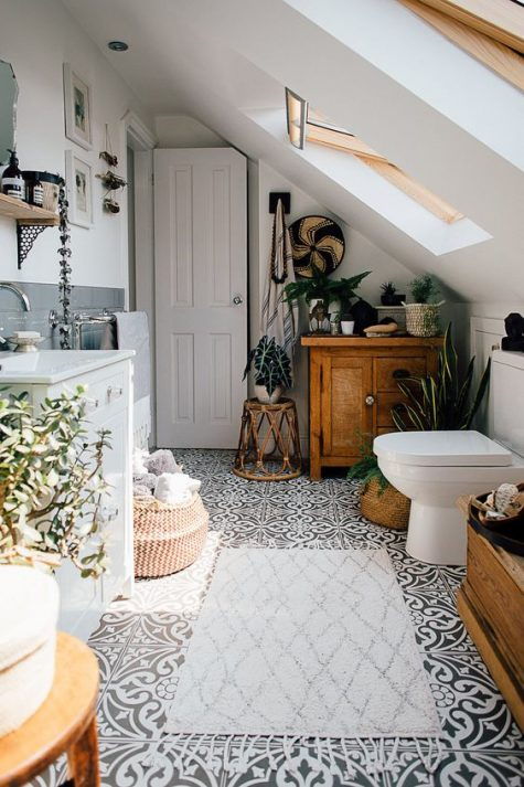 a boho bathroom with potted greenery and succulents, baskets for storage, a mosaic tile floor and some rich stained wooden items