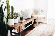 a boho chic entry with a boho rug, a dark stained wooden bench, potted cacti, printed pillows