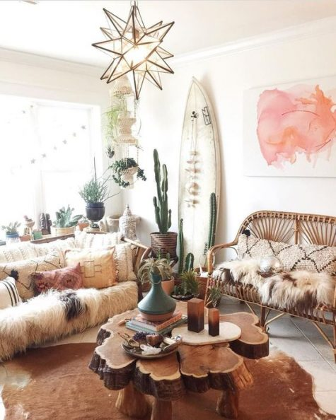 a boho chic living space with a surf board, rattan furniture, wood slice coffee table and potted greenery and cacti