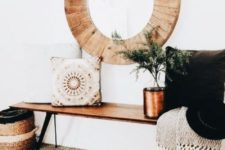 a boho chic space with a printed folksy rug, a wooden bench, an embroidered pillow, a basket, a blanket and a wood clad mirror