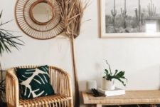 a boho desert entryway with rattan furniture and mirror in a frame, a dried palm leaf, baskets for storage, a cactus artwork
