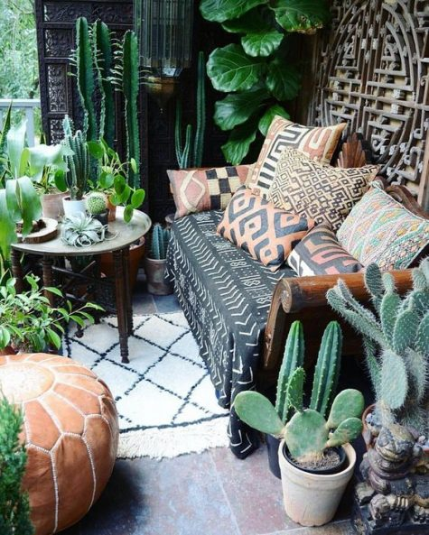 a boho desert porch with cacti, greenery, statement plants, a sofa with printed pillows and a carved wooden table