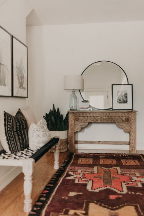 a boho entryway with a vintage inlay console table, a woven bench and matching contrasting pillows, artworks and a large rug