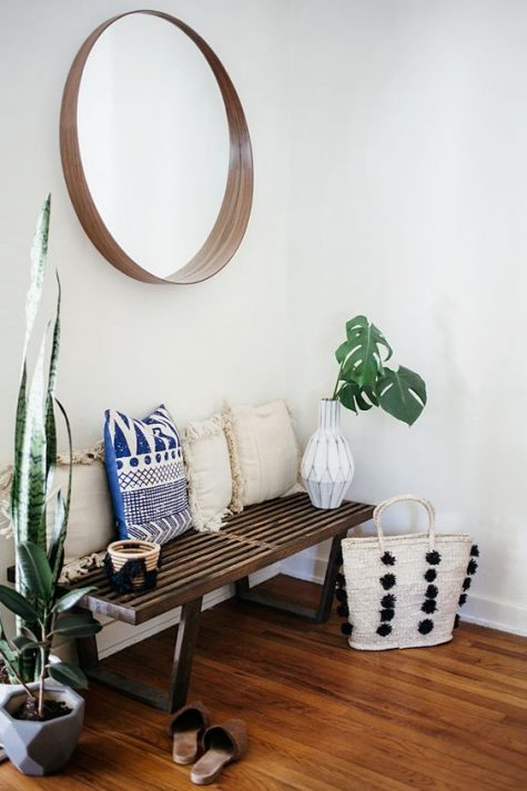 a boho hallway with a dark stained bench, boho pillows with fringe, a mirror in a plywood frame and potted plants