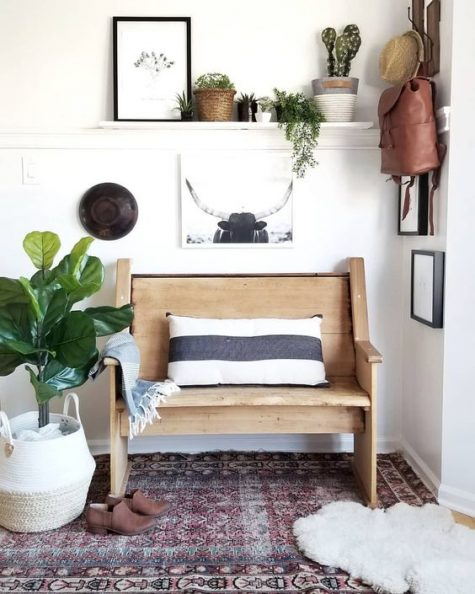 a boho hallway with a small wooden bench, potted cacti and succulents, a gallery wall, a boho rug and faux fur